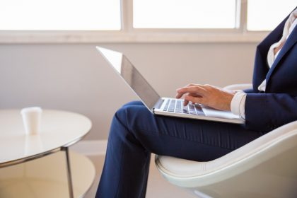 Businesswoman working in office lounge. Diverse business women sitting in armchair, using laptop and other gadget. Office lounge concept